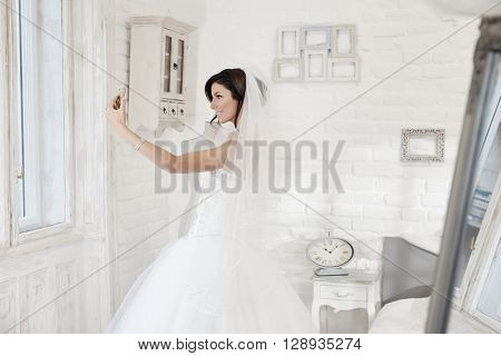Beautiful bride making selfie by mobilephone. Side view.