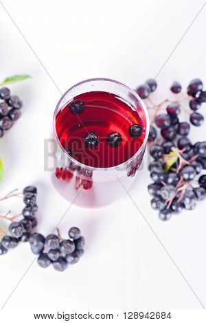 Overhead view on glass of aronia juice with berries in the light background