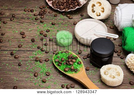 Anti-cellulite cosmetics with caffeine. Wooden spoon with green sea salt and coffee beans, natural body scrubs, skin care cream, body scrubbers, towels. Spa and cellulite busting products. Copy space