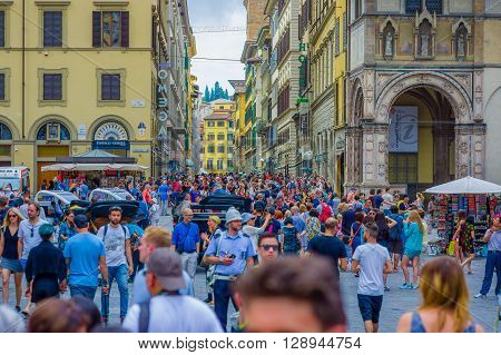 FLORENCE, ITALY - JUNE 12, 2015: Crowded square on Florence, all tourists walking around trying to visit this nice city, heads