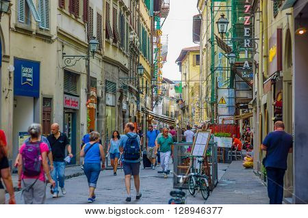 FLORENCE, ITALY - JUNE 12, 2015: Tourists and people crossing into a comercial street, a lots of shops on the sides. A new contruction on the right. Pinturesque street.
