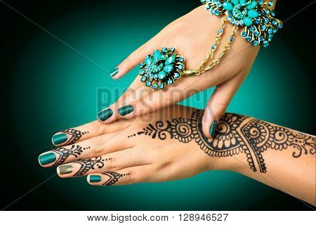 Woman Hands with black mehndi tattoo. Hands of Indian bride girl with black henna tattoos. Hand with perfect turquoise manicure and national Indian jewels. Fashion. India