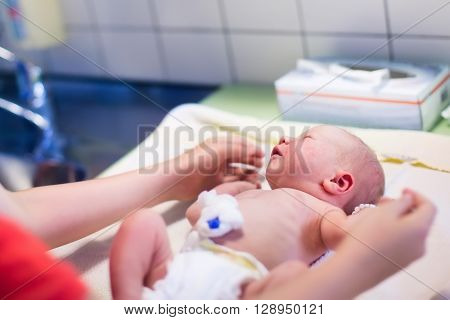 Newborn child washed and examined after birth in hospital. New born baby with umbilical cord clamp at sponge bath. Diaper change for infant in clinic. Mother washing little child and changing nappy. poster