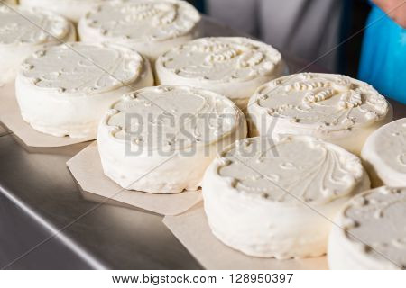 White cakes with ornament. Cakes on pieces of paper. Simple cake decoration idea. Quality cakes from local plant.