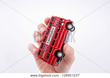 Hand holding a London double decker bus on a white background