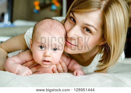 Portrait of happy mother and baby at home. The child is 2 months