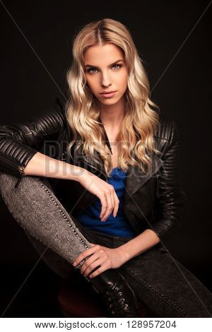 fashion blonde biker woman in leather jacket resting her hand on knee and looks at the camera on black studio background