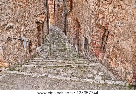 picturesque old narrow alley with staircase in the medieval village Castiglione d'Orcia, Siena, Tuscany, Italy