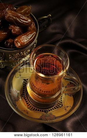 Arabic black tea and dates. Middle eastern food and cuisine.