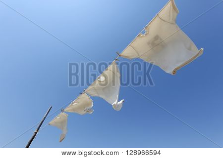 White t-shirts hanging on the clothesline against blue sky