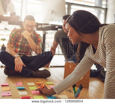 Woman Writing On Notes For Workers On Floor