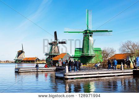 Zaanse schans, Netherlands - April 1, 2016: Windmills in Zaanse Schans, North Holland, traditional village, tourists, blue sky
