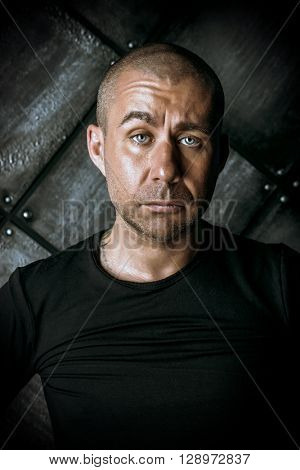 Close-up portrait of a man in black clothes over dark grunge background.