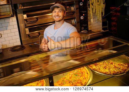 Handsome pizzaiolo standing at kitchen in pizzeria.