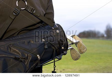 Golfclubs In Black Bag On Back Of Golfer