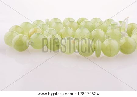 Green stone beads on a white background