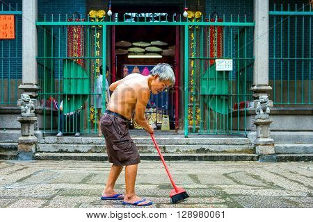 Hong Kong China - September 25 2007: An old man sweeps the entrance of the Tin Hau Temple in the Yau Ma Tei quarter.