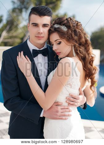 Young loving couple,the groom in dark suit and bow tie and the bride in a beautiful white wedding gown,a brunette with long curly hair,a beautiful tiara and earrings in their ears,stand embracing near swimming pool with blue water