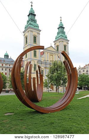 BUDAPEST HUNGARY - JULY 13: Art Installation and Inner City Parish Church in Budapest on JULY 13 2015. Contemporary Art Sculpture in Front of Gothic Romanesque Church in Budapest Hungary.