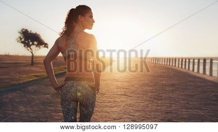 Fit Young Woman Walking On Seaside Promenade In Sunset