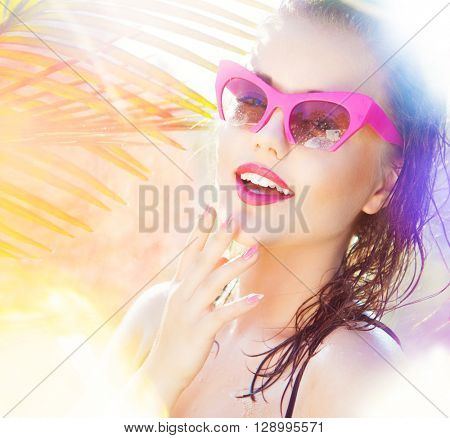 Colorful summer portrait of happy young attractive woman wearing wet sunglasses. wet hair beauty and fashion concept. natural bokeh and light effect
