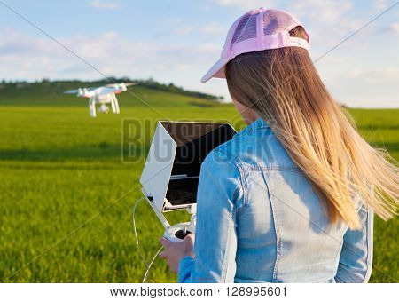Young woman holding radio controller with tablet and sun shade flying drone over a field. Aerial video and photography maker. Hovering aircraft in the background.