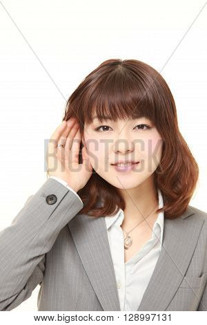 young businesswoman with hand behind ear listening closely