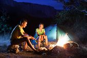 Couple in camping with campfire at night poster
