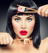 Sushi. Fashion art portrait of beauty model girl eating Sushi rolls, healthy japanese food. Beautiful woman holding chopsticks with sushi. Sexy female portrait with perfect make up, bright lips poster