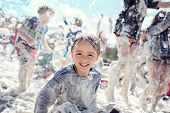 Boy smiling and laughing covered in soap suds at a summer foam party poster