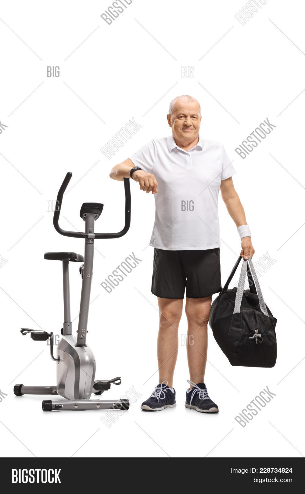 e767ddfc94e Full length portrait of a senior with a sports bag leaning on an exercise  bike isolated
