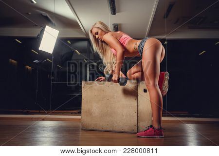 Blond Female With Sexy Buttocks Standing On Knee And Holding One Dumbbells.