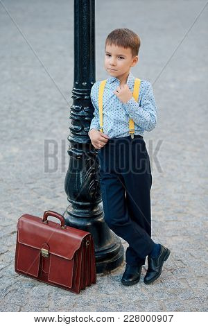 Concept Future Bank Clerk. Full Length Boy Portrait In Dark Blue Pants, Baby Blue Shirt And Yellow S