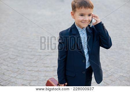 Concept Future Businessman. Portrait Of Smiling Businessman In Formal Wear Standing On Pedestrian St