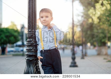 Fashion Full Length Boy Portrait In Dark Blue Pants, Baby Blue Shirt And Yellow Straps, Standing On