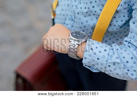 Silver Watch On The Hand Of Future Businessman In Blue Shirt, With Brifcase And Yellow Suspenders. T