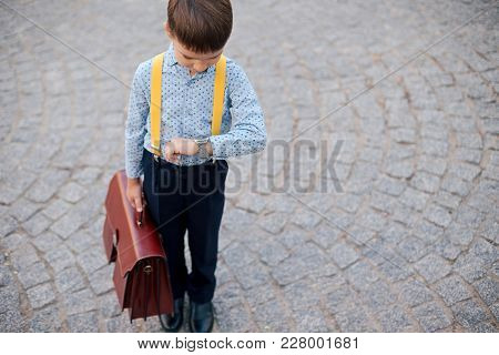 Concept Future Businessman. Boy Portrait In Dark Blue Pants, Baby Blue Shirt And Yellow Suspenders,