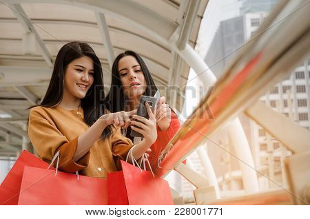 Two Beautiful Cheerful Asian And Caucasian Young Woman With Mobile Smart Phone, Credit Card And Hold