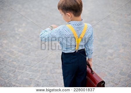 Concept Future Businessman. Back View Boy In Dark Blue Pants, Baby Blue Shirt And Yellow Straps, Sta