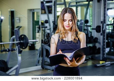 Fitness, Workout, Gym, Technology And Lifestyle Concept - Young Woman Holding A Clipboard With A Pla