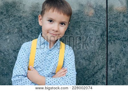Close-up Boy, Future Businessman, Wearing Yellow Suspenders, Dark Blue Pants And Blue Shirt Against