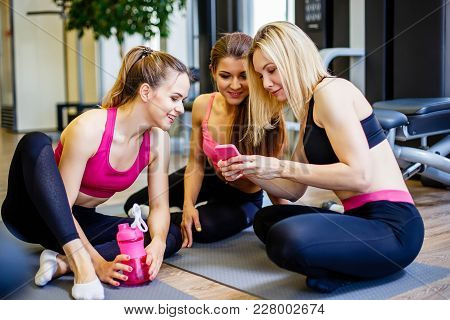 Group Of Girls In Fitness Class Looking At Smartphone And Smiling. Female Friends In Gym Taking A Br