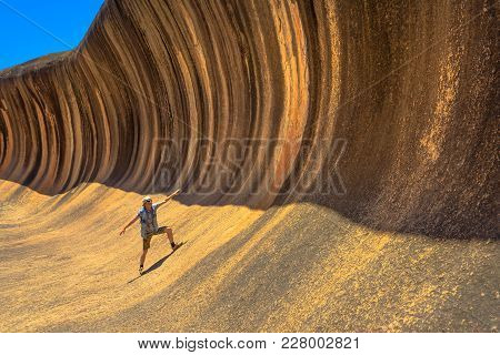 A Sporty Man Enjoying Surfing On The Wave Rock, A Natural Rock Formation That Is Shaped Like A Tall