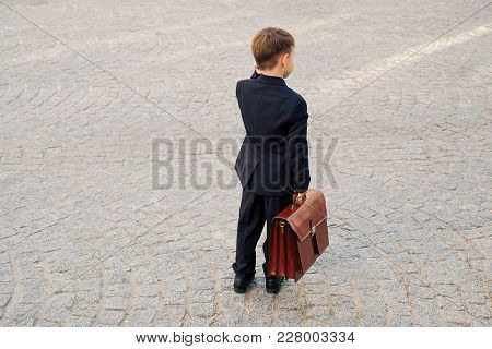 Concept Future Businessman. Back View Of  Smiling Businessman In Formal Wear Standing On Pedestrian