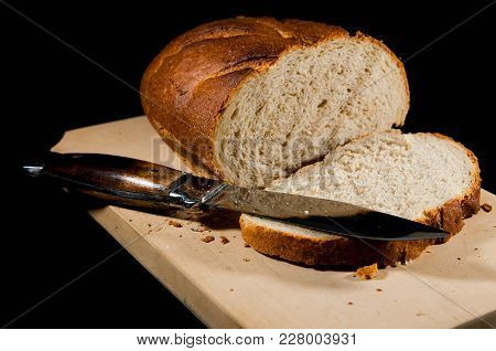 Fresh Sliced Rye Bred With A Sharp Knife Isolated On Black Background.