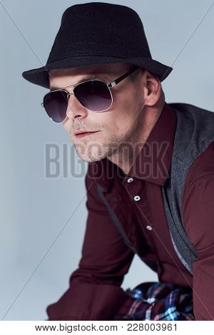 Portrait Of Casual Male Dressed In A Shirt, Waistcoat And Sunglasses Over Grey Background.