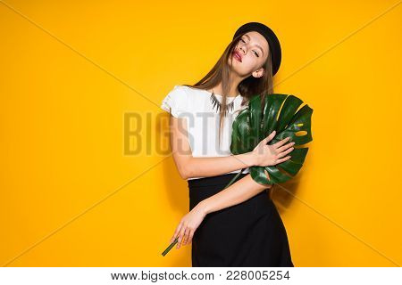Attractive Stylish Girl In A Black Hat Posing On A Yellow Background, A New Collection Of Clothes