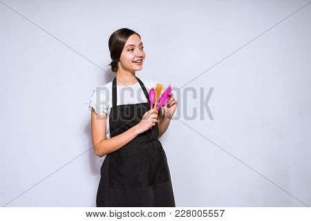 Young Girl Cook In Black Apron Holds In Hands Cooking Tools