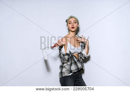 Attractive Funny Girl In A Plaid Shirt Paints A Wall With A Roller In Her New Apartment