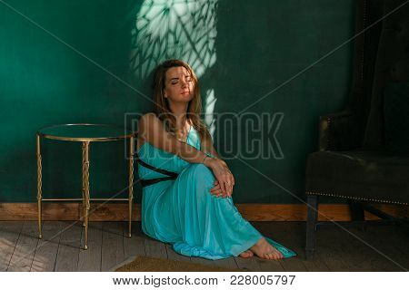 Sweet Woman Sits On Floor Barefoot Against Green Wall. Relaxing In Sunbeams. Horizontal Shot With Co
